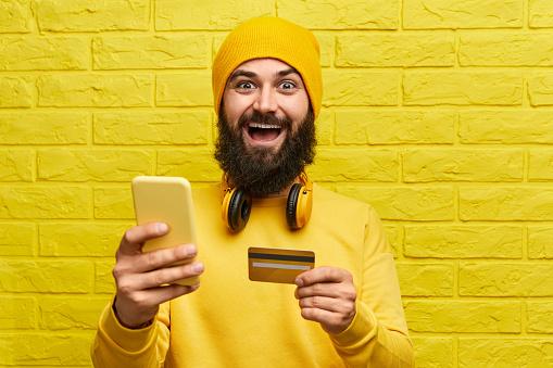 istock Cheerful man shopping online 1152823413