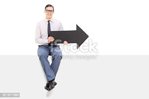 istock Cheerful man sitting on a panel and holding an arrow 521877385