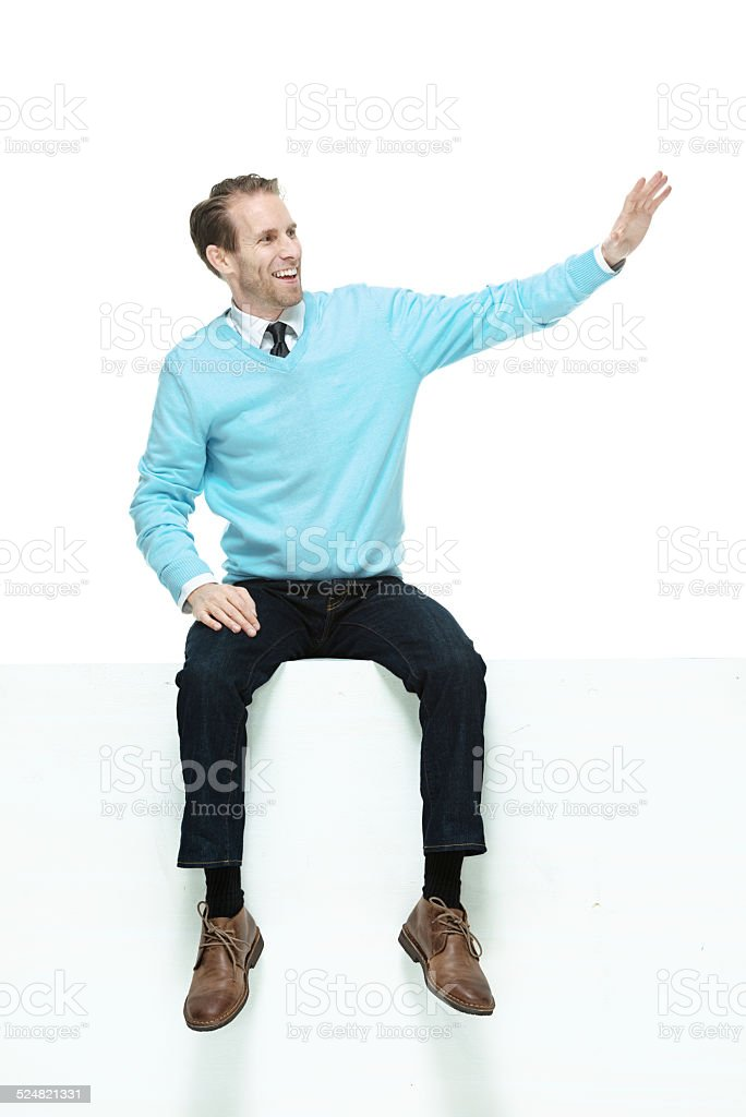 Cheerful man sitting on box waving hand stock photo