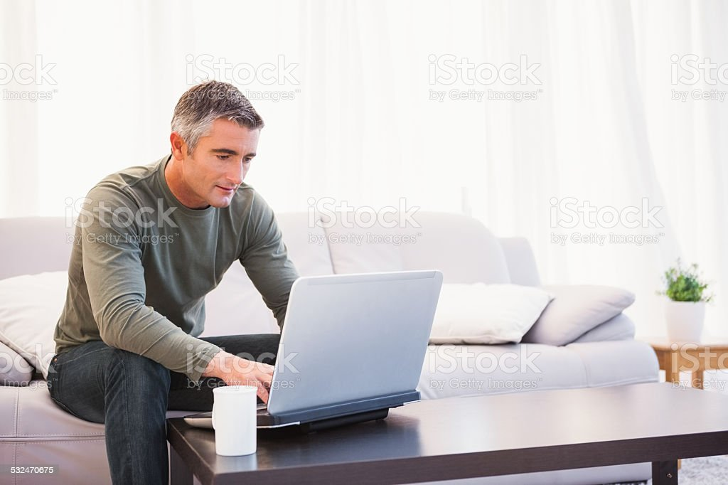 Cheerful man sitting on couch using laptop stock photo