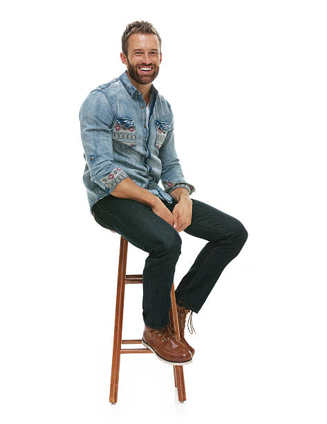 Cheerful man sitting on stool stock photo
