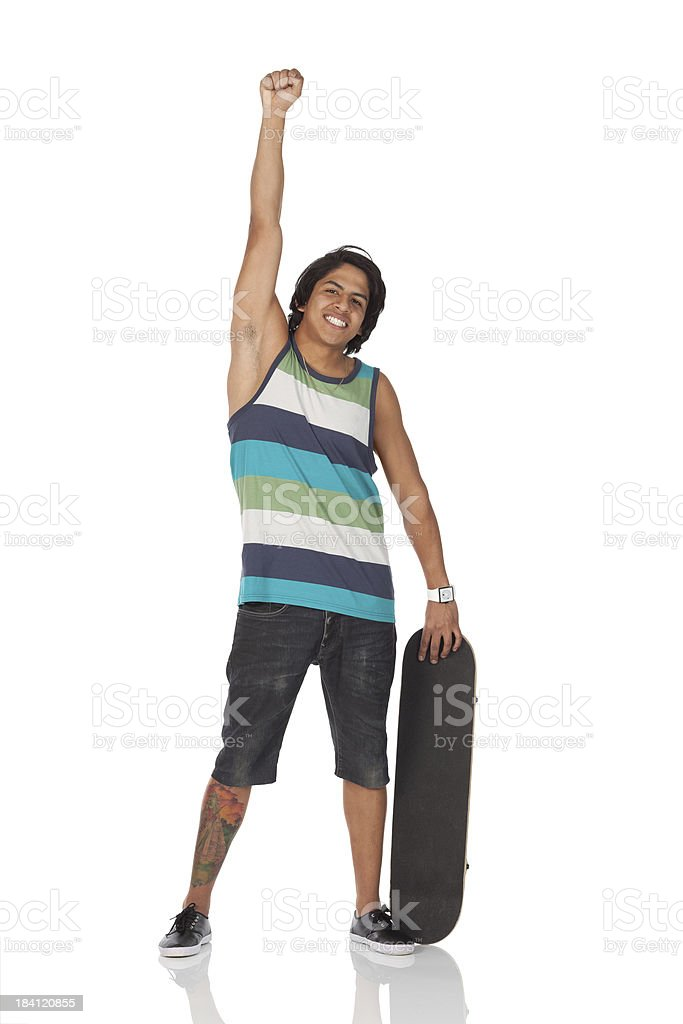 Cheerful man standing with a skateboard royalty-free stock photo