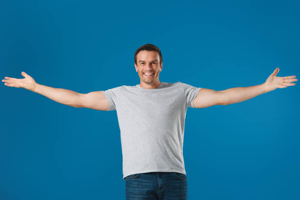 cheerful man standing with open arms and smiling at camera isolated on blue cheerful man standing with open arms and smiling at camera isolated on blue arms outstretched stock pictures, royalty-free photos & images