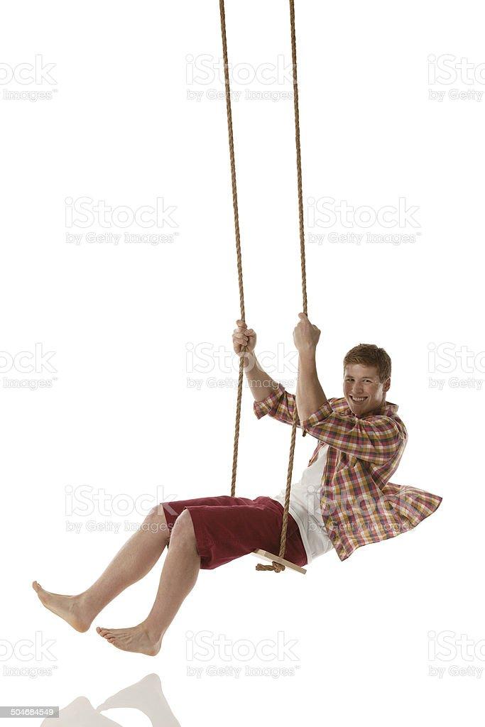 Cheerful man swinging stock photo