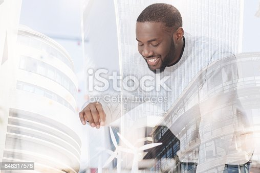 istock Cheerful man touching little windmill 846317578