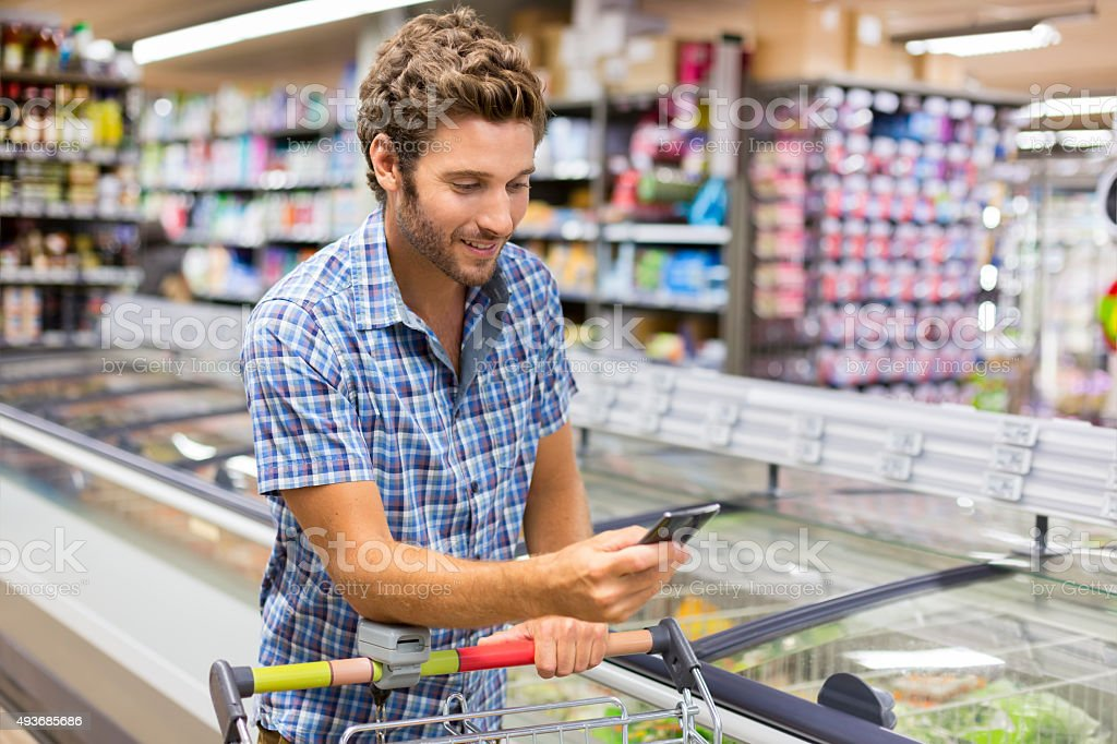 Cheerful man using app mobile phone in grocery store stock photo