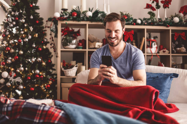 Cheerful man using his smart phone while relaxing in bed in the morning stock photo