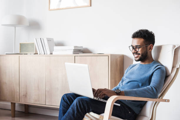Cheerful man using laptop computer at home stock photo