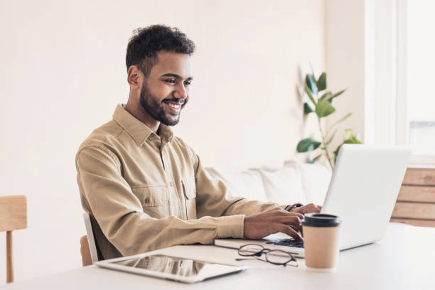 Cheerful man using laptop working at home online stock photo