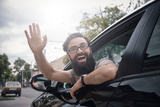 gai homme agitant pendant que vous conduisez une voiture - homme faire coucou voiture photos et images de collection
