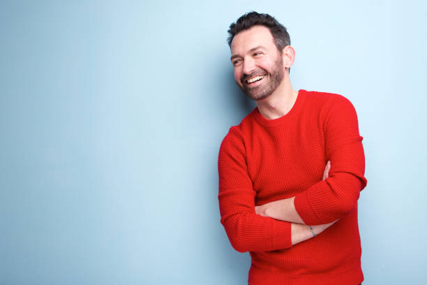 cheerful man with beard laughing against blue background - ritratto uomo foto e immagini stock