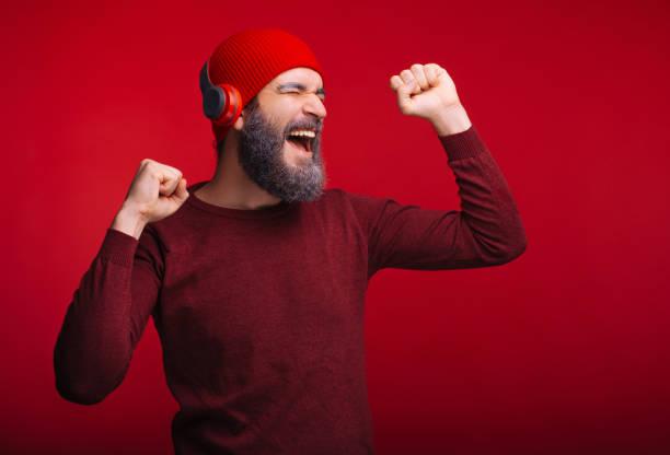 glad man med skägg lyssnar musik på hans trådlösa hörlurar - happy indie pop bildbanksfoton och bilder