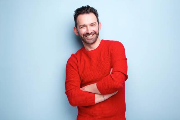 fröhlicher Mann mit Bart posiert vor blauem Hintergrund – Foto