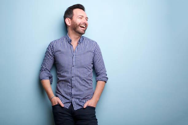 fröhlicher Mann mit Bart posieren gegen blaue Wand – Foto