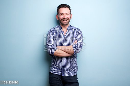 Portrait of cheerful man with beard posing against blue wall with arms crossed