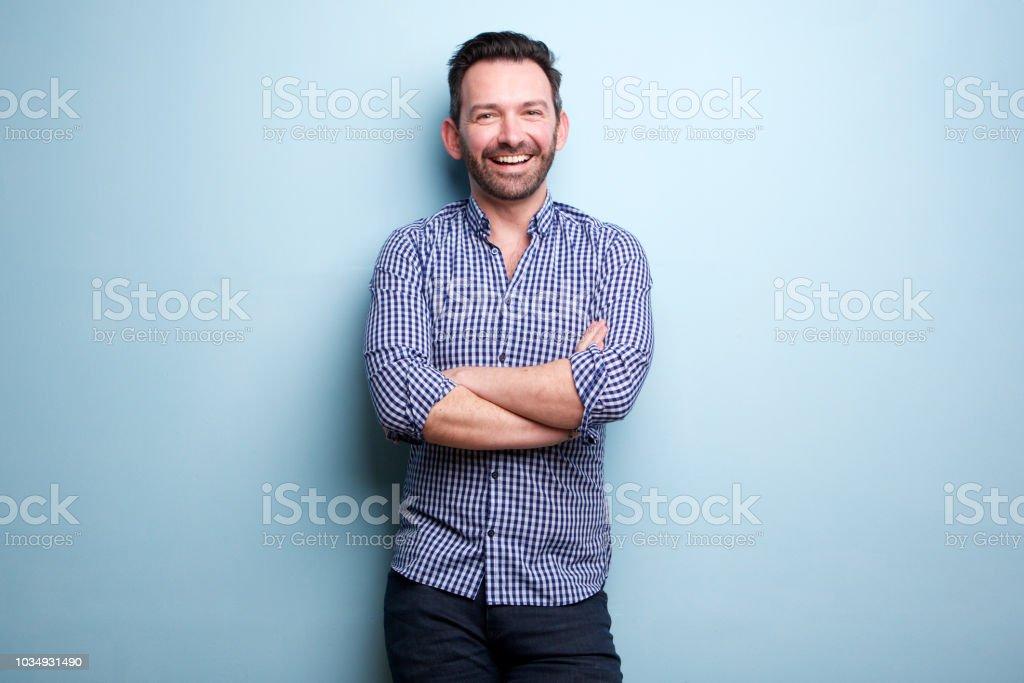 gai homme avec barbe posant contre le mur bleu avec les bras croisés - Photo