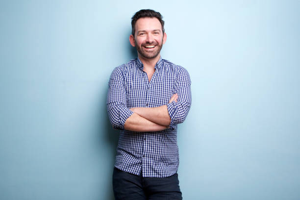 cheerful man with beard posing against blue wall with arms crossed stock photo