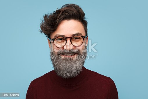 Handsome man in glasses and with beard in silver glitters smiling at camera.