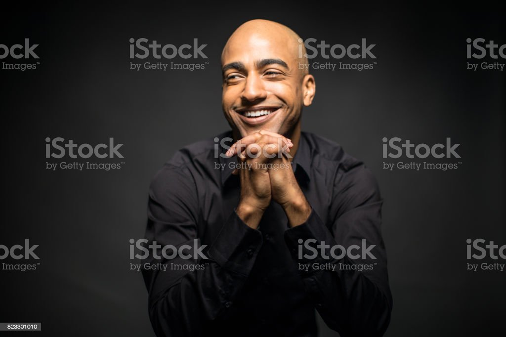 Cheerful Man With Hands Clasped Looking Away stock photo