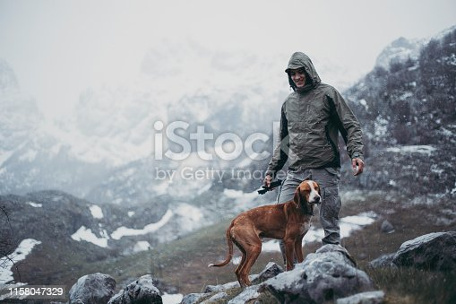 Hiking man with a dog on a mountain trip during the rain and snow.
