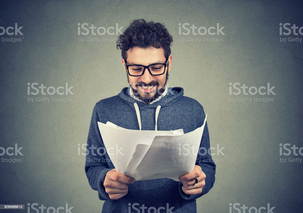 Cheerful man with papers on gray stock photo