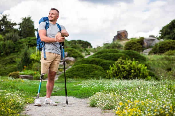 Cheerful man with prosthesis standing with Nordic walking sticks stock photo