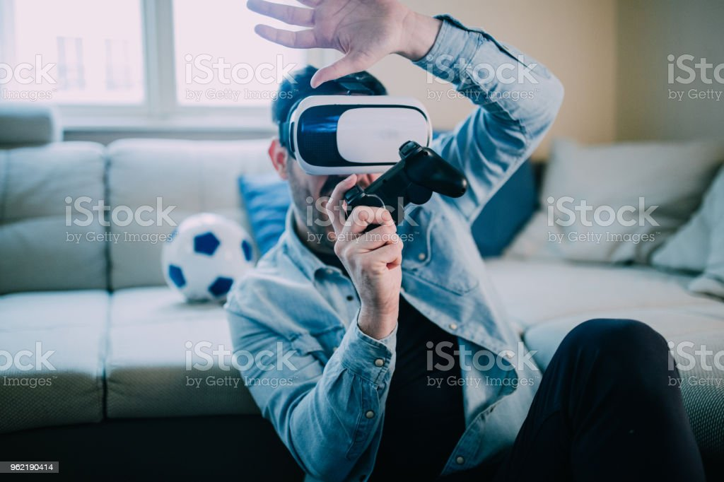 Cheerful man with virtual reality glasses playing video games stock photo