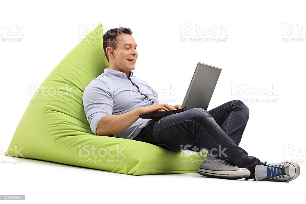 Cheerful man working on laptop stock photo