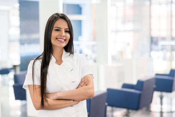 cheerful manager of a hair salon looking at camera smiling with arms crossed - beautician stock photos and pictures