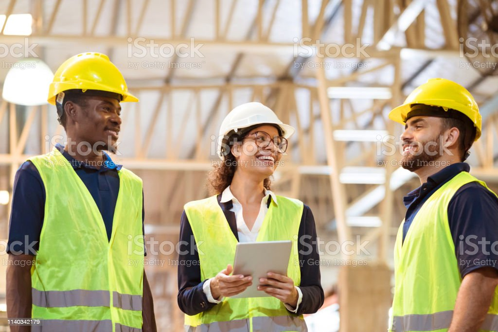 Cheerful manager working with workers in factory Cheerful manager looking at male worker. Expertise are wearing reflective clothing and hardhats. They are working in factory. 20-24 Years Stock Photo