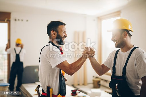 961745166istockphoto Cheerful manual workers greeting each other at construction site. 968822758
