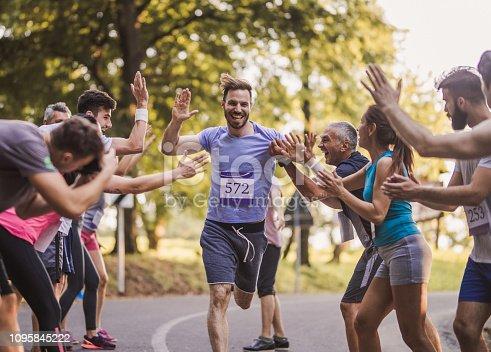 670054434istockphoto Cheerful marathon runner greeting group of athletes at finish line. 1095845222
