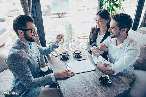 istock Cheerful married couple is getting a car key from a car dealer in the showroom and signing contract, all are dressed in formal outfits, smiling 936401036