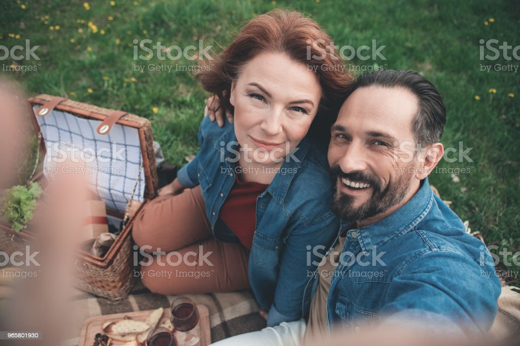 Cheerful married couple making selfie on meadow - Royalty-free Adult Stock Photo