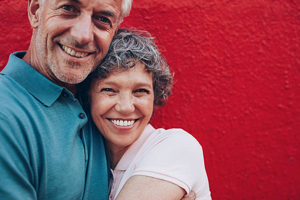 cheerful mature couple embracing each other - adults only stock photos and pictures
