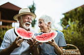 Cheerful senior couple having fun while eating watermelon in the backyard.