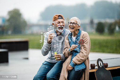 Playful senior couple having fun while blowing bubbles at skate park.