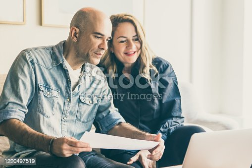 Cheerful mature couple having video call via laptop. Cheerful middle aged people talking about house renovation through video call. New house project, renovation concept