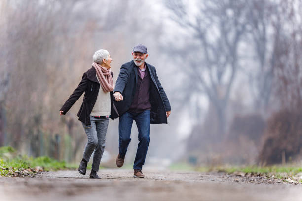 Cheerful mature couple holding hands and running in nature. stock photo