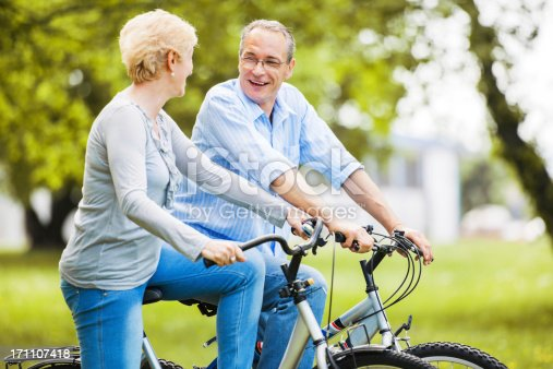 1029243348 istock photo Cheerful mature couple riding bicycles in park 171107418