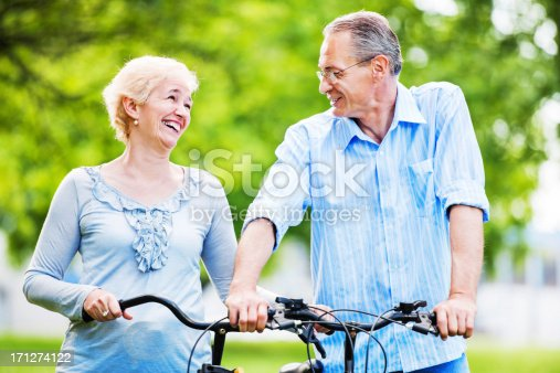 1029243348 istock photo Cheerful mature couple riding bicycles in park. 171274122