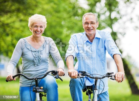 1029243348 istock photo Cheerful mature couple riding bicycles in park 175590967
