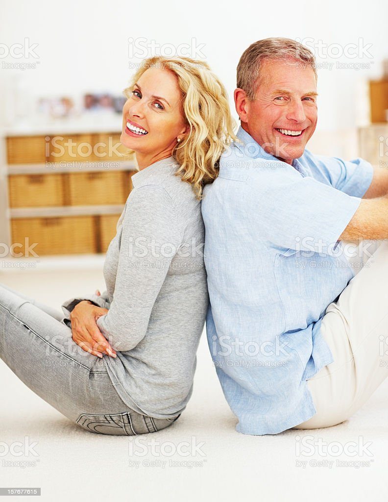 Cheerful mature couple sitting back-to-back at home royalty-free stock photo