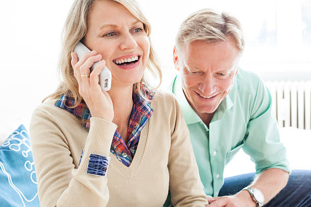 Cheerful mature couple speaking on a phone Cheerful mature woman talking on phone with a man sitting on sofa, indoors. cordless phone stock pictures, royalty-free photos & images