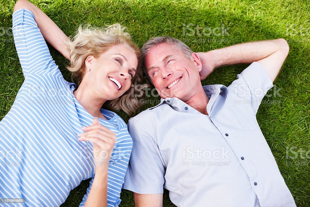 Cheerful mature couple spending time together on grass stock photo