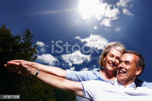 510491454 istock photo Cheerful mature couple together having fun against sky 157677206
