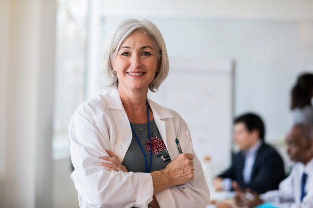 A cheerful mature female doctor stops for a photo After the board meeting, an attractive mature female doctor stops for a photo for the hospital newsletter. lab coat stock pictures, royalty-free photos & images
