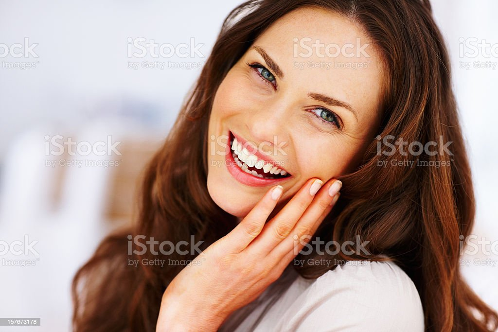 Cheerful mature female with hand on chin stock photo