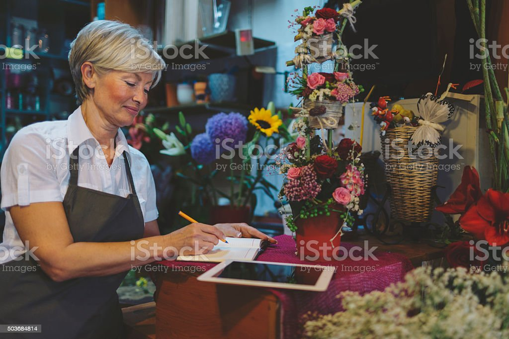 Cheerful mature florist making order stock photo