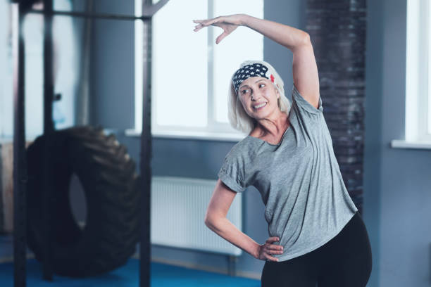 Cheerful mature lady stretching during training session stock photo